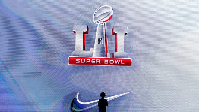 A young boy stands in front of a large video screen looking at the Super Bowl LI logo, inside the fan zone at the convention center in Houston, Texas, USA, 29 January 2017.