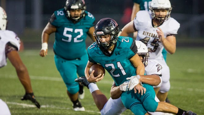 Gulf Coast High School running back Richie Dimarzio is taken down by Riverdale defense at Golden Gate High School in Naples where the Sharks took on the Riverdale Raiders on Thursday, September 28, 2017.