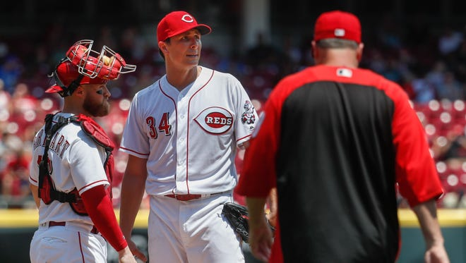 Cincinnati Reds starting pitcher Homer Bailey (34) waits to be relieved by manager Bryan Price, right, in the fifth inning of a baseball game against the Washington Nationals, Sunday, July 16, 2017, in Cincinnati. (AP Photo/John Minchillo)