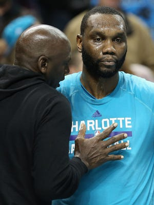 Michael Jordan, owner of the Charlotte Hornets, talks to player Al Jefferson during a game. Jefferson has been suspended by the NBA.