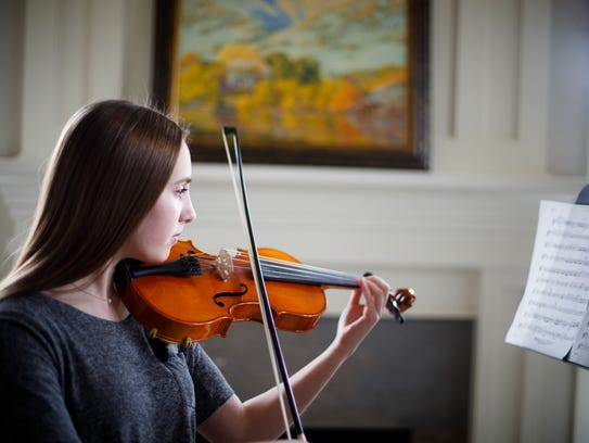 Abby Karras, 14, practices the violin at her home in