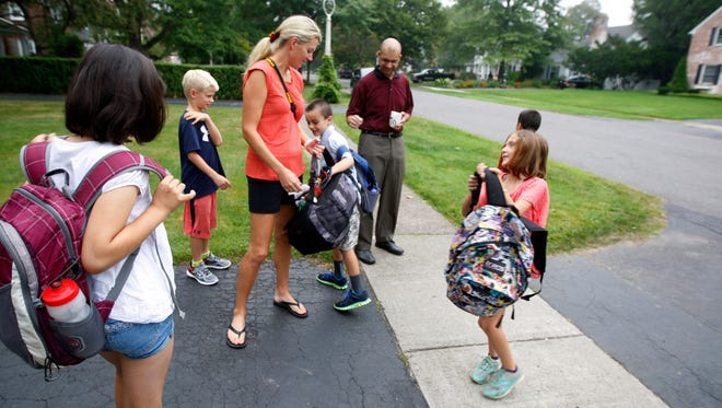 Leslie Servé jokes about how heavy her son, Trevor's backpack is with Deven Rao while students and parents wait in a driveway on Bonnie Brae Ave.  Behind her is her son, Trevor, and preparing to compare her backpack is Maddie Horowitz and Athena Rao, back to camera.  Also at the same stop was Austin Rao and dad, Arvind.  The Rao children are triplets.