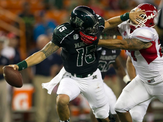 Hawaii quarterback Ikaika Woolsey is sacked by Fresno State linebacker Donavon Lewis at Aloha Stadium.