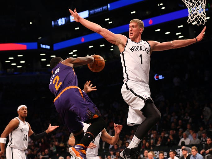 Suns guard Eric Bledsoe (2) passes behind Nets forward Mason Plumlee (1) during the first quarter.