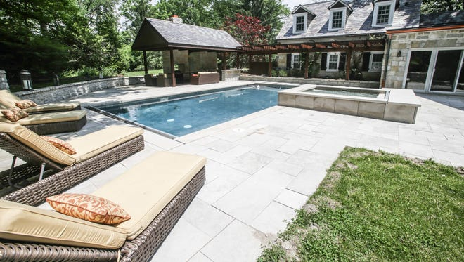 The homeowners installed a salt-water pool and hot tub for outdoor entertainment. A fireplace and pool house are part of the area.