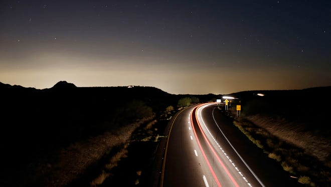 Taillights streak down Interstate 17 on a moonless night south of Black Canyon City. The southern horizon is illuminated with light from the metro Phoenix area.