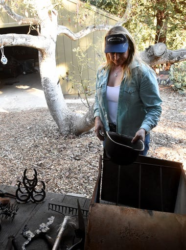 Stacy Hyatt sorts through the few tools items recovered from her home in Wheeler Canyon after the Thomas Fire destroyed the property she was renting.