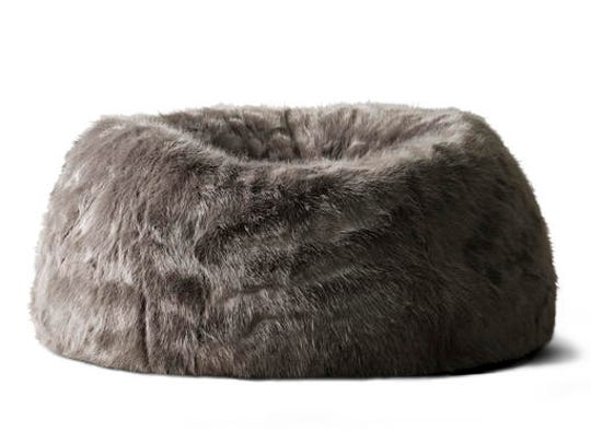 This undated photo provided by RH, Restoration Hardware, shows a squooshy, faux fur bean bag chair. The chair satisfies several of the hygge trend's characteristics, including comfort, warmth and softness.