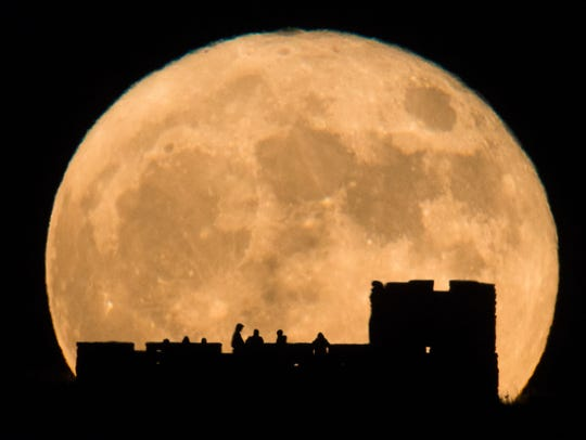 People watch the supermoon rise behind Coronado Heights near Lindsborg, Kan., on Nov. 14, 2018.