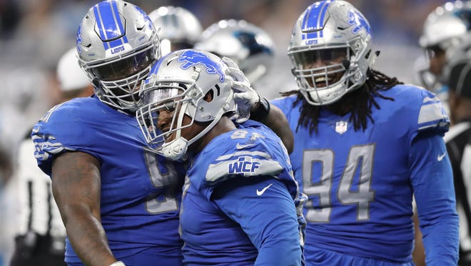 Lions' A'Shawn Robinson, left, and Akeem Spence, center, celebrate a stop in the fourth quarter of the 27-24 loss to the Carolina Panthers at Ford Field on Oct. 8, 2017.