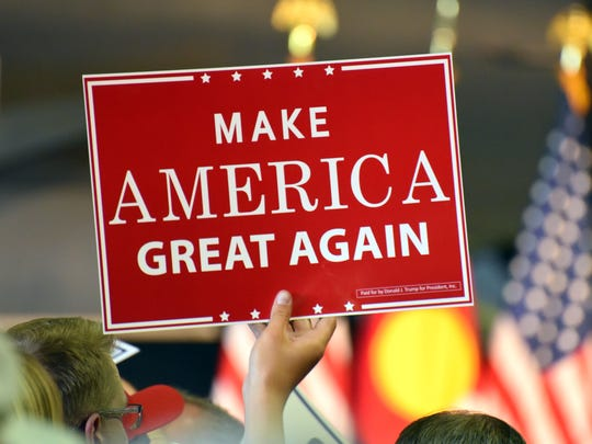 A Donald Trump supporter holds a campaign sign during