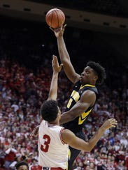 Iowa's Tyler Cook, top, shoots over Indiana's Justin