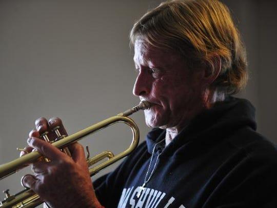 Greg Ellis plays his trumpet at James Robertson Apartments