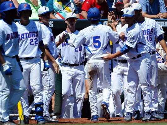 Florida Gators infielder Dalton Guthrie (5) enters the dugout after scoring the first run of the game in the third inning in the 2015 College World Series at TD Ameritrade Park.