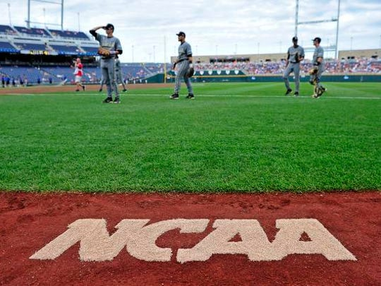 the NCAA logo is seen on the ground as Vanderbilt players warm up against Virginia in the College World Series at TD Ameritrade Park, Tuesday, June 23, 2015, in Omaha, Neb.