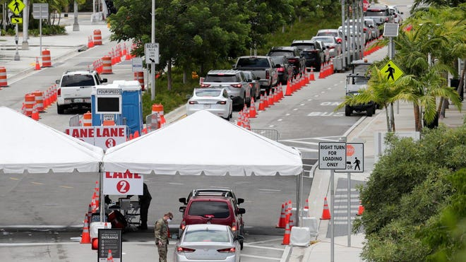 Vehicles wait in line at a COVID-19 testing site at the Miami Beach Convention Center during the coronavirus pandemic, Sunday, July 12, 2020, in Miami Beach, Fla. Fla. on Sunday reported the largest single-day increase in positive coronavirus cases in any one state since the beginning of the pandemic.