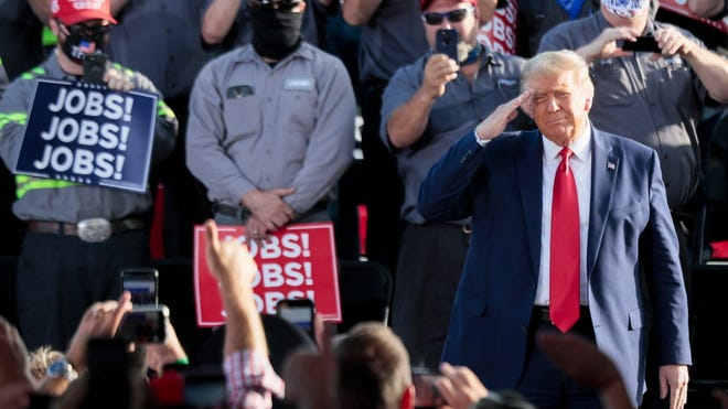 """President Donald Trump salutes the crowd during the """"Fighting for the American Worker"""" rally on Monday, Sept. 21, 2020, at the Wright Bros. Aero Hangar at the Dayton International Airport in Vandalia, Ohio."""