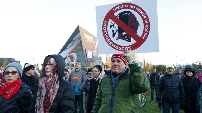 In this Oct. 24, 2019, file photo, Native American leaders protest against the Redskins team name outside U.S. Bank Stadium before a game between the Minnesota Vikings and the Washington Redskins in Minneapolis.