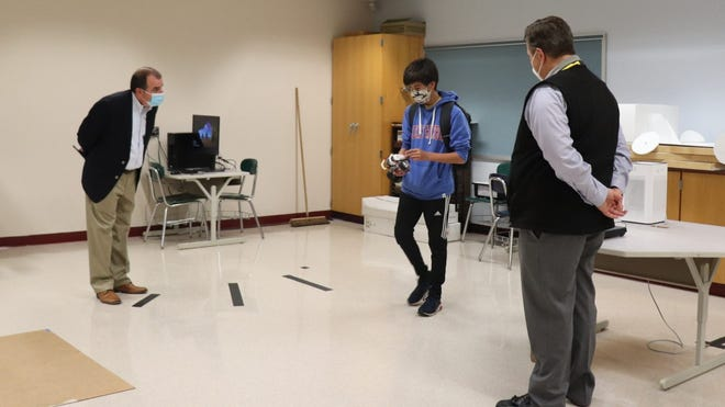 Mark Rodgers (left) and Archie Gleason (right), of Exelon, talk with ninth grade student Brayden Myers about his robotics project.