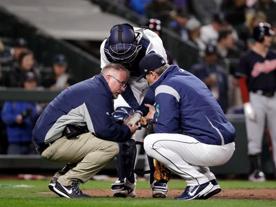Seattle Mariners catcher Mike Marjama is examined after being hit by the bat of the Indians' Edwin Encarnacion during Thursday's season opener.