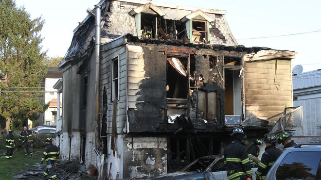 Mount Vernon, N.Y., firefighters work at the scene of a fatal fire that began around 3 a.m. Oct. 29, 2013, and killed four members of the Ureña family.