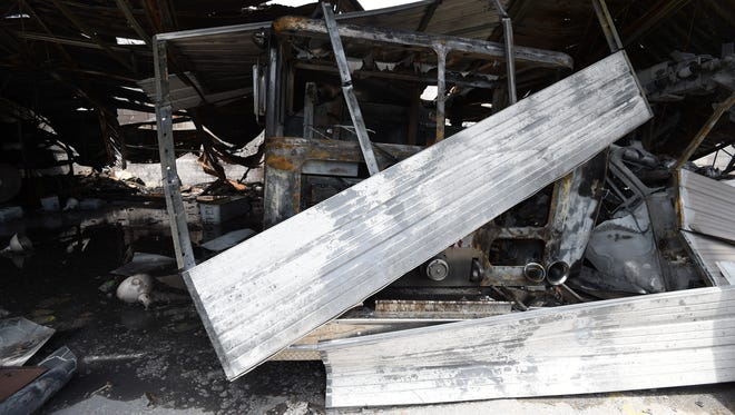 The heat twisted metal of a garage door sits atop the paint stripped cab of a fire truck Tuesday at the Gainesville Volunteer Fire Department. The department's building caught fire early tuesday morning. The cause of the fire remains under investigation.