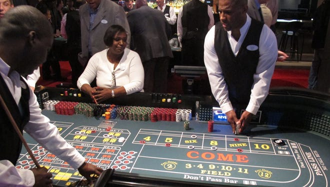 Dealers prepare to pay winning bets at a Revel Casino Hotel craps table in Atlantic City on May 21, 2012.