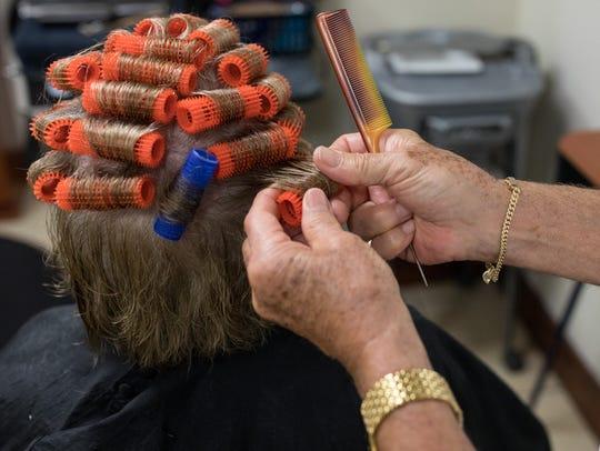 Daniel Ruidant puts curlers in Kay Rowling Long's hair