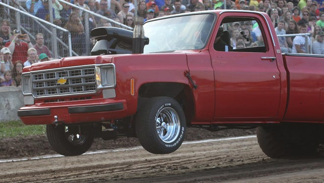 The front end of the 1993 Chevy of Jake Waldhart of Greenwood comes off the ground as Waldhart finishes his pull at the Marshfield Parish Pull at Marshfield Fairgrounds Park on Friday, July 10, 2015.