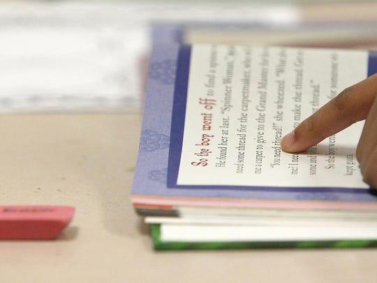 A student follows along in her book in Cassie Elliott's third-grade class at Alexander Elementary School on Tuesday.