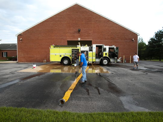 Mike Smith, a five-year veteran firefighter at Middletown's Volunteer Hose Co. Fire Station 1, power washes a hose as he and other volunteers clean a fire truck Tuesday.