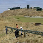 Technicians adjust a long video camera slider rail on Thursday on the 18th hole at Chambers Bay golf course in University Place, Wash. In its bid to take over the U.S. Open from NBC, Fox promised innovative coverage.