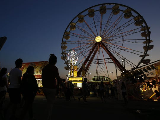 Crowds head to the midway Friday, Aug. 14, 2015, during