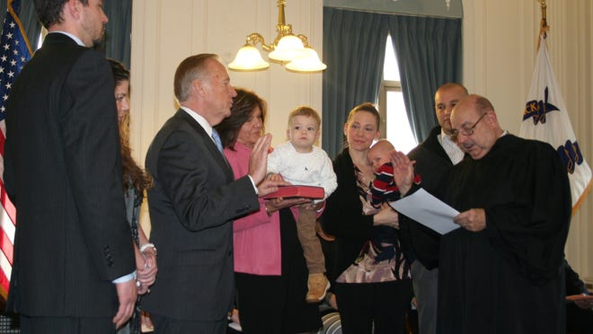 Retired Superior Court Judge C. Judson Hamlin administers the Oath of Office to New Brunswick Mayor James Cahill, who is joined by his family, on Friday.
