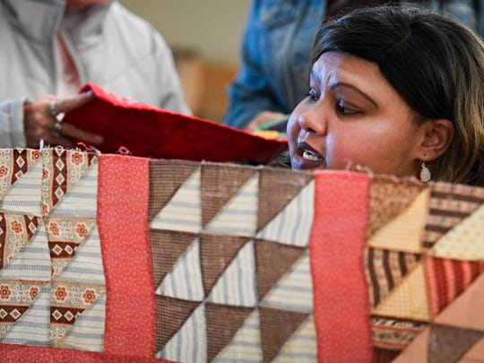 Britney Westbrook, curator for the Evansville African-American Museum displays a 1860's vintage quilt block during a lecture about African-American quilters and the Underground Railroad at the Henderson County Public Library Saturday, February 11, 2017.