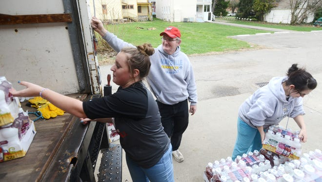 Teddy Newell watches as Amanda Renick, right, and Ivy Lyons unload a truck at the Salvation Army in Zanesville recently. Newell has been volunteering at the Salvation Army for a year, helping out where he can.