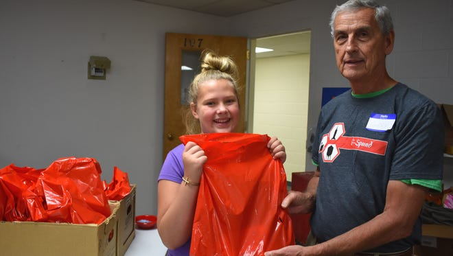 Ashtyn Van Arnam, a sixth grader who volunteered during the school supply giveaway, picks up a bag of basic essentials to head back to school.