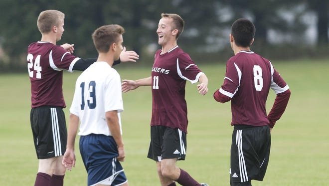 Manitowoc Roncalli's Evan Mihalakakos (13) walks away as N.E.W. Lutheran players celebrate after Ben Malme (11) scored a goal during the first half of Thursday's game in Manitowoc.