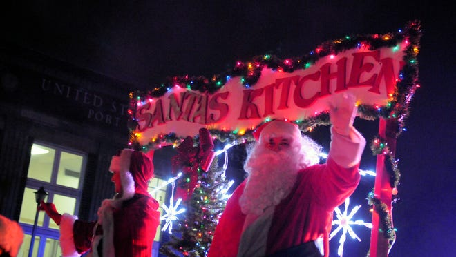 Santa Claus and Mrs. Claus wave to people as they ride in the second annual Main Street Port Clinton lighted parade Saturday.