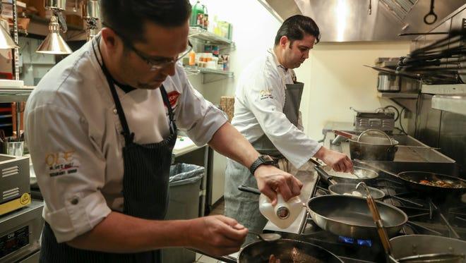 Yaniel Martinez and cousin Fernando Martinez work on preparing each of their own spins during a mystery food box cookoff at Artesana Vino Tapas Y Mas in Westport Village. Feb. 16, 2018