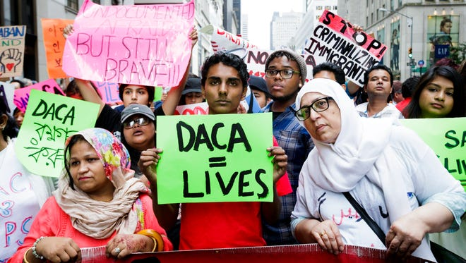 People gather for a rally and protest to mark the fifth anniversary of the Deferred Action for Childhood Arrivals (DACA) program near Trump Tower in New York, New York, on August 15, 2017. President Trump is considering ending the program.