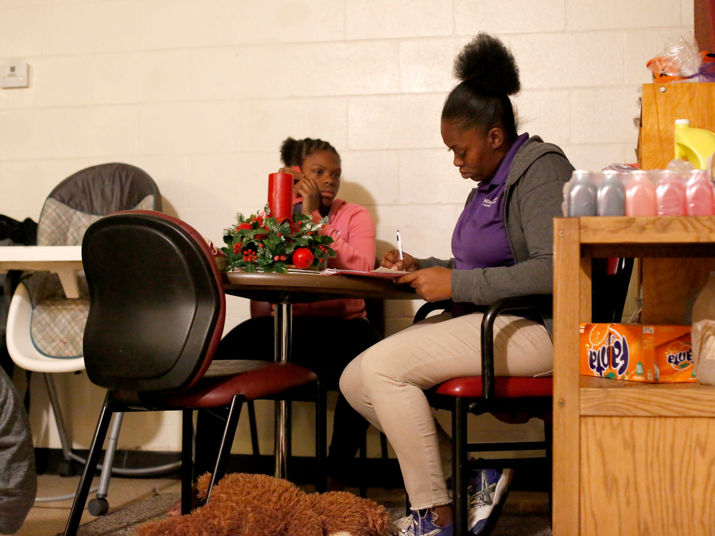 Porsche Robinson (right) goes over school papers with her daughter Trinity, 13, in their apartment Nov 15.