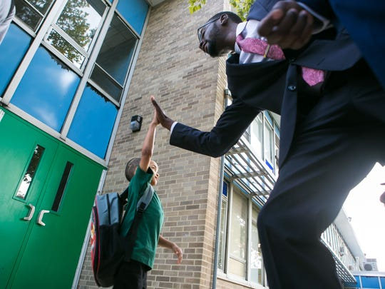 UD graduate student Garry Johnson gives a student a high five as he joins other black males in suits for Suit Up. Show Up., where several dozen African-American men stepped up to model what success looks like by welcoming students at EastSide Charter School on their first day of school.