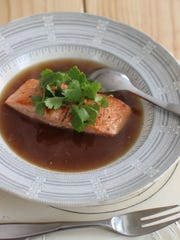 Seared king salmon is served with lemongrass porcini jus.