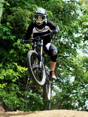 Downhill rider Patrick Tait rides over a step on a