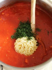 This Sept. 14, 2015 photo shows tomato, orzo and dill soup in Concord, N.H. This dish is from a recipe by Katie Workman. (AP Photo/Matthew Mead)