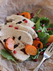 Wine-poached chicken breast top a salad.
