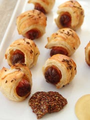 A puff pastry pig in a blanket is topped with caraway seeds.