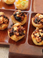 Puff pastry hors d'oeuvres are filled with Gorgonzola cheese, chopped prunes and crumbled bacon.