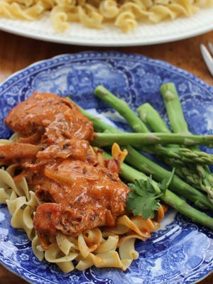 Chicken paprikash with egg noodles sports a sauce rich with tomatoes and paprika. Stirring sour cream into it just before serving transforms it into a true comfort food.